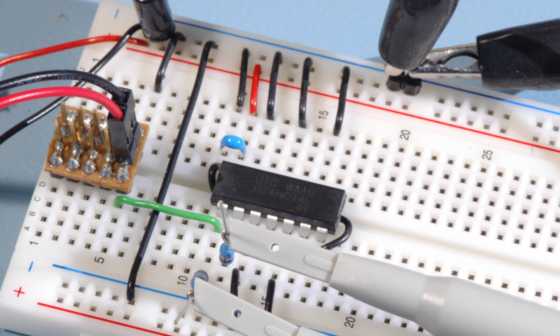 Breadboard with 74HC14 and attached oscilloscope probes